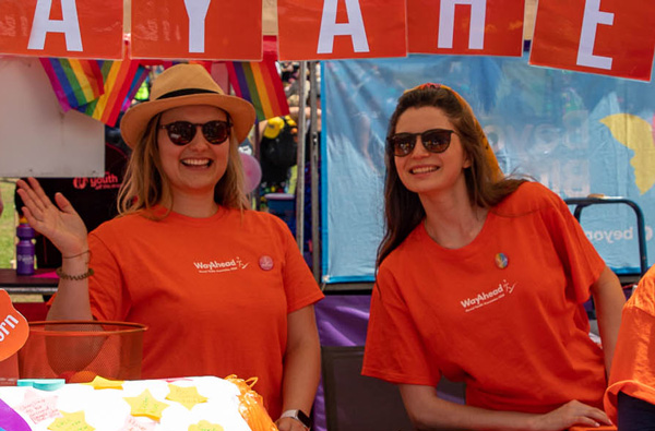 Two smiling WayAhead staff members stand at a mental health and wellbeing-themed stall for Mardi Gras' Fair Day